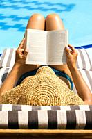 Woman reading book by swimming pool