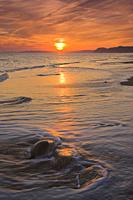 Sunset on the beach at Burton Bradstock looking towards Lyme Regis in the Distance Dorset