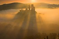 Corfe Castle back lit by the sun causing long shadows to appear as it rises out of the mist at dawn Purbeck Dorset