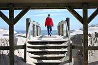 Woman walking on to a beach through a boardwalk shelter  Lavalette, New Jersey, USA