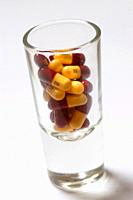 Medicine tablets and pills in shot glass close up