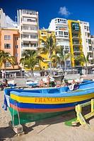 View of the Las Canteras beachfront in Las Palmas de Gran Canaria with a colorful fishing boat in the foreground. Las Palmas, Gran Canaria, Canary Isl...
