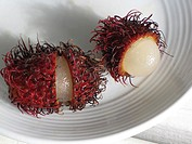 Rambutan fruit cut open on plate, Big Island, Hawaii, USA