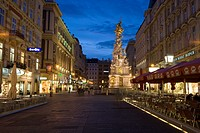 Nighttime view of shops and cafes on Graben Street and view of the Plague or Pestsaule Column, Vienna, Austria