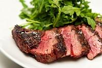 Rare Sliced Steak and Arugula on a White Plate
