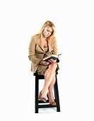 Young blonde woman in business suit reading a book sitting on a stool