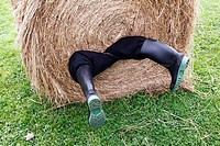 A man rolled up in a hay bale with his legs hanging out.