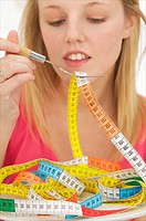 Young blond woman with long hair eating a colored tape out of a plate to evoke the concept of diet and weight problems, concept image