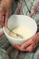 An old woman stirring homemade icing in a bowl on her lap