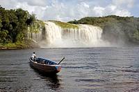 VENEZUELA GUAYANA NATIONAL PARK CANAIMA CANAIMA VILLAGE A Pemon tribe man while sailing with his boat at Canaima lake just in front of a big waterfall...