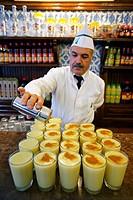 Barman putting Cinnamon on drinks of ´Boza´  The Vefa Bozacisi Shop, Istanbul, Turkey