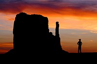 A Cowboy watches the sunset over the Mittens in Monument Valley on the southern border of Utah with northern Arizona  The valley lies within the range...