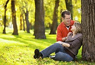 Happy young couple sitting at the park, looking at each other lovingly
