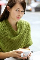 Beautiful young woman relaxing with her cappuccino outdoor