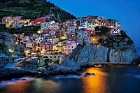 Manarola view at dusk across harbor with light reflection on water