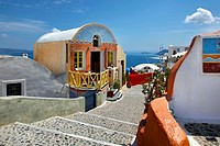 Colorful store and stone steps leading down path with ocean view in Oia, Santorini, Greece