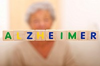 Alzheimer written in bright letters and behind, blurred the silhouette of a senior woman