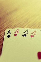 The four ace cards from a pack of cards on a wooden table. No sharpening applied.