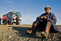 Old Mongolian man, dressed in a traditional way, eating during a rest in a long bus ride, Mongolia
