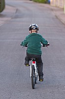 A seven year old boy riding his BMX bike in the Uk