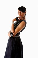 Beautiful modern classy African American female fashion model in black dress with silver chains and biker gloves looking sideways thinking, isolated