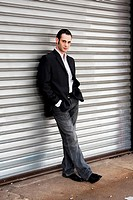 Handsome casual business man standing in front of and leaning against silver metal garage door with hands in pocket