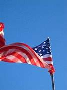 The American Flag blowing in the wind against a blue sky