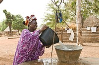 African Bassari women with headscarf hauling water from a well , Salemata village, Bassari country, Senegal, Africa