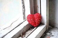 loneliness concept - red heart on white obsolete windowsill
