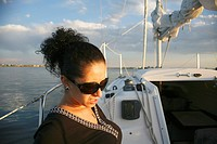 A beautiful young hispanic woman sits on a sailboat enjoying an evening cruise