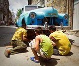Man man repairs a broken down car in the street while another man and a boy look on in Havana, Cuba