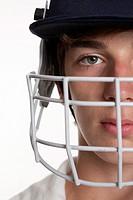 Portrait of teenage cricketer in protective helmet and visor