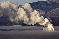 One of Megalopolis thermoelectric power plants shrouded in a mixture of fog, and smog from its own chimneys, Arcadia, central Peloponnese, Greece  The...