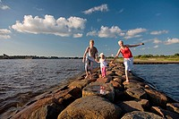Mother with Kid Girl and Teenage Boy Holding Hands Walking on Pärnu Pier by Sea, Estonia