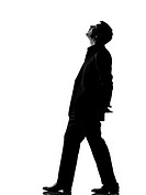 silhouette caucasian business man walking musing looking up expressing behavior full length on studio isolated white background