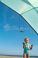Little girl playing under a sunshade at the beach, Camargue, France
