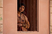 Indian woman with cellphone in her hand, looking through barred window, Phalodi Rajasthan, India