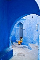 Street scene with a girl sitting on a threshold of a house, Chefchaouen, Morocco