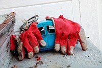 An old blue tin VW-beetle toy car lies abandoned on a shelf in a garden, covered with red garden gloves