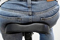 person wearing jeans sitting on bicycle saddle