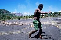 Fisherman on a black sand beach preparing his nets, Sulphur Bay Village, Tanna Island, Vanuatu