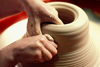 close up of a potter´s hands as he carefully shapes his clay on the turning wheel