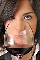 young brown woman smelling a glass of red wine