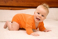 Five month old baby crawling on bed