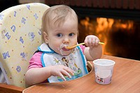 One year old dirty baby girl in high chair eating yogurt using spoon