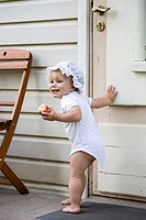 Happy One Year Old Baby Girl Standing Outside by Wooden Door with Apple in Hand