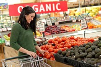 Attractive woman grocery shopping, in the produce section  An ´Organic´ sign in the background shows she is shopping for organic produce