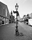Street Entertainer Playing a Flute Whilst Hanging From a Lamp Post, Lewes, Sussex, England