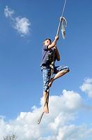 Nine year old boy swinging on a rope swing Atiamuri, New Zealand