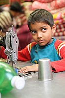 child labourer, young boy sewing , the nepalis , life in kathmandu , kathmandu street life , nepal
